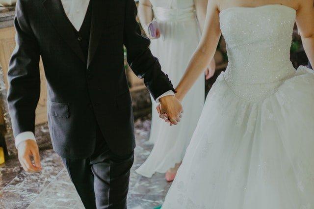 Nevesta  ženích kráčajú po kostole a držia sa za ruky.jpg