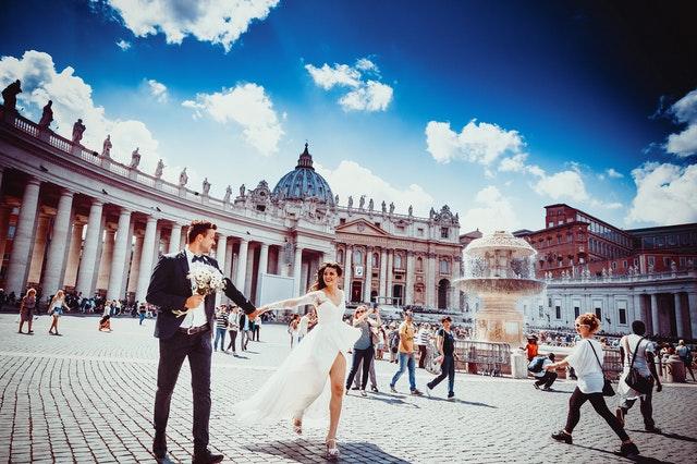 Muž v smokingu a žena v svadobných šatách sa držia za ruky a kráčajú po meste.jpg