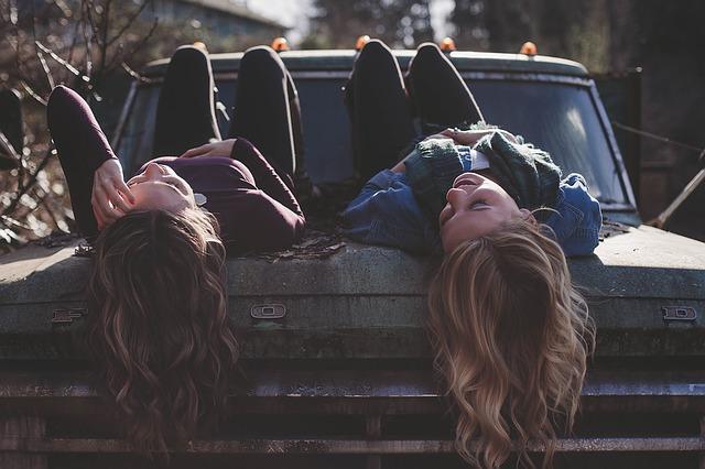 Dve dievčatá s dlhými vlasmi ležia na kapote starého auta