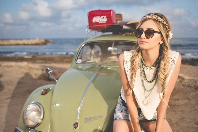 Žena so zapletenými vrkočmi, sedí na kapote auta, ktoré stojí na pláži