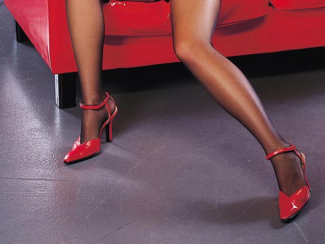Žena v čiernych pančuchách a červených lodičkách sedí na červenom koženom gauči