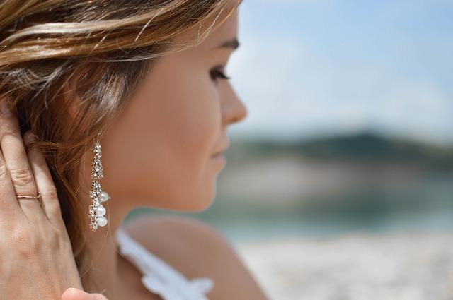 Mladá žena s hnedými vlasmi má v uchu striebornú náušnicu s perlami.jpg