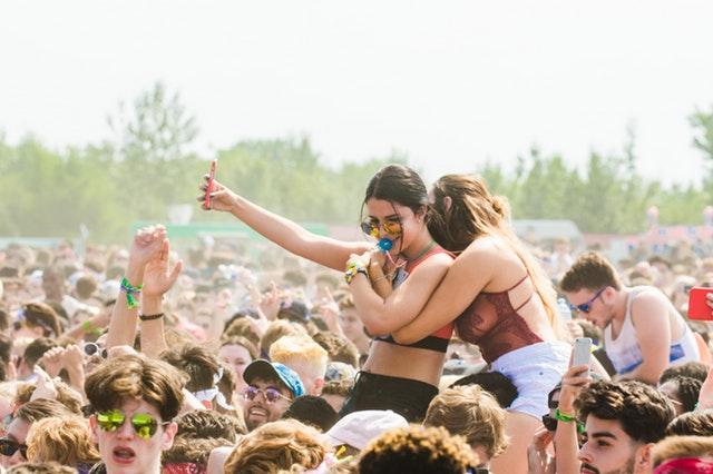 Ženy v plavkách sedia na ramenách mužov, na hudobnom festivale.jpg