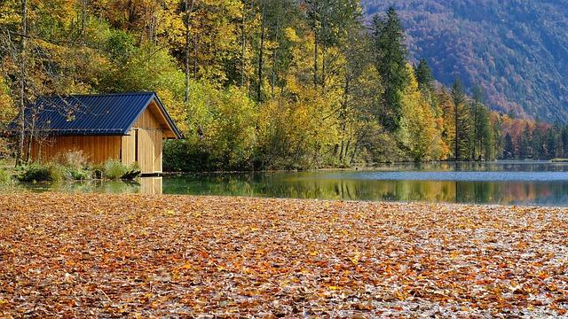 Mobilný dom obložený drevom na brehu jazera v jeseni.jpg