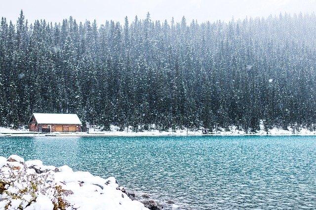 Jednoposchodová chata na brehu jazera so zasneženou strechou.jpg